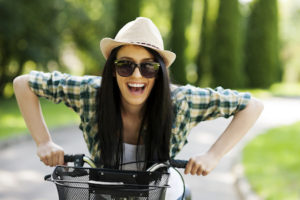 Woman riding a bike smiling after getting a tooth filled from the restorative dentistry menu at Sound to Mountain Dental in Tacoma, WA.
