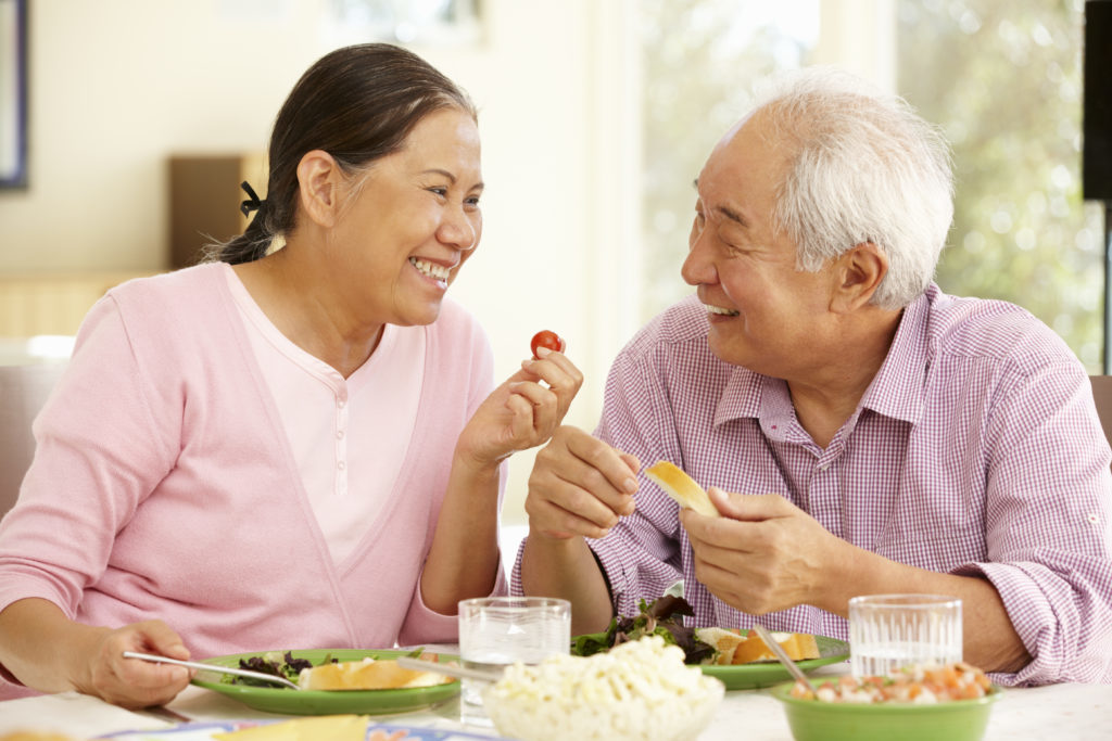 Older Asian couple eating with confidence because of the dental implants they received from Dr. Hickey at Sound to Mountain Dental in Tacoma, WA.