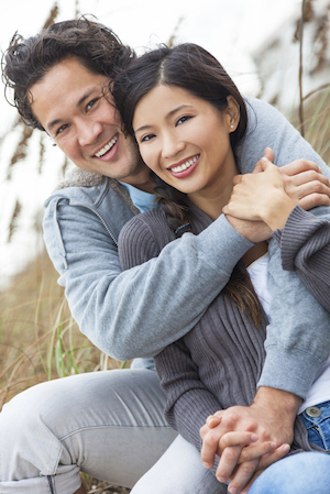 Attractive Asian couple sitting, hugging and smiling over the smile makeovers they received with the help from Dr. Hickey from Sound to Mountain Dental in Tacoma, WA.