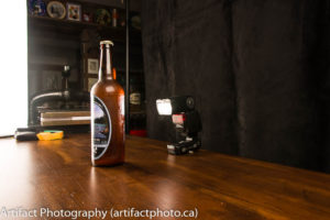 Speedlight flash positioned directly behind bottle