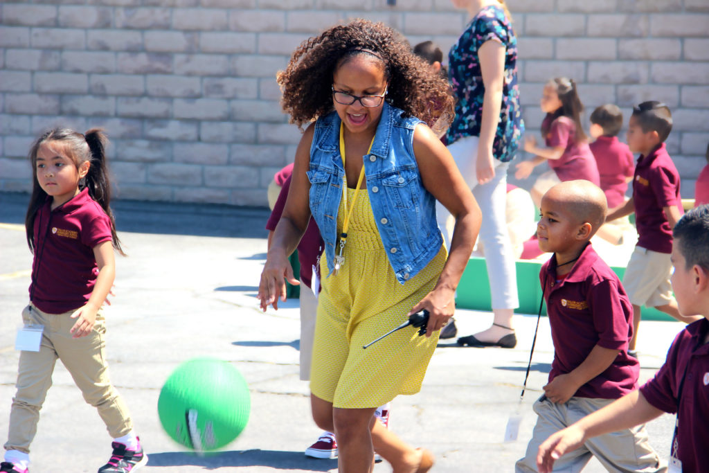 Ms. Guy plays soccer with some of her students.