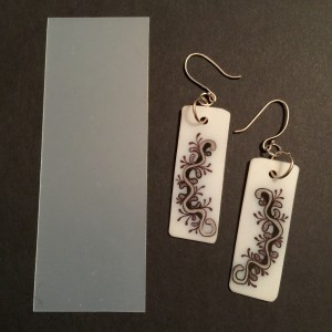 Shrink plastic! Each earring in the right started as a larger rectangle as seen on the left.