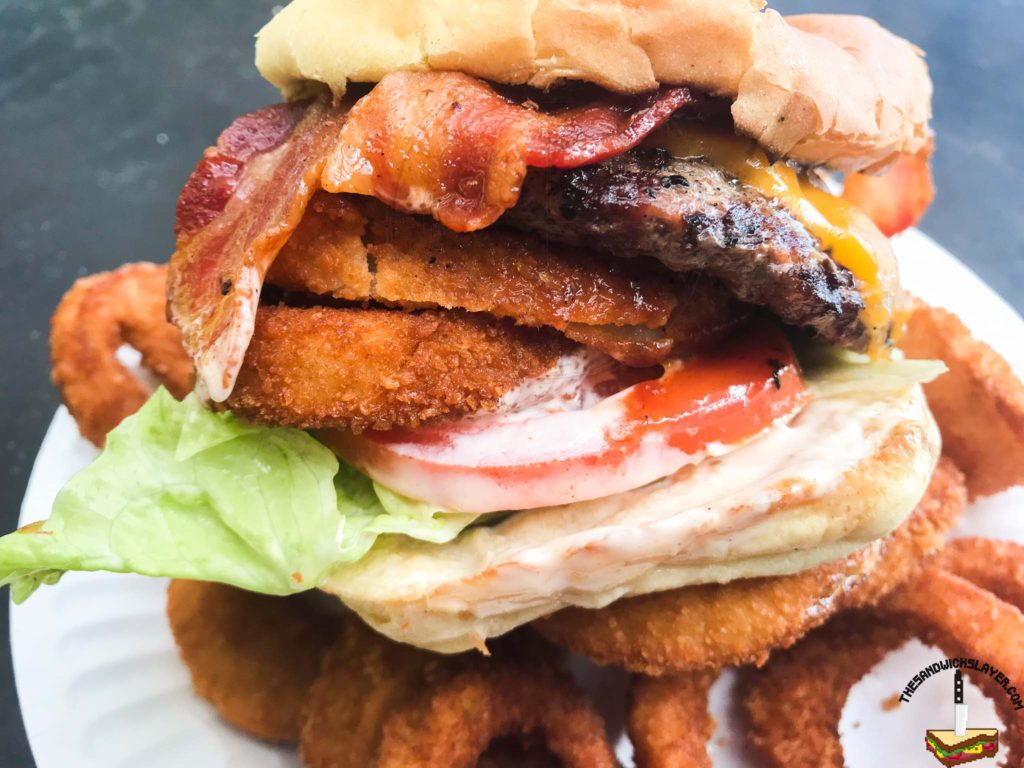 TK Burgers Tombstone Burger. Hamburger with onion rings, bacon, cheddar, and BBQ sauce