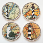 """Set of 4 Lighthouses: Ocracoke, Hatteras, Bodie & Cape Lookout. Set includes box perfect for gift giving! Absorbent stone coasters are approx 4"""" round and have cork backing."""