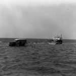 Charlie Mac driving through sea tide off the ferry courtesy NPS Collection