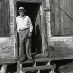 Tommy Howard, postmaster for 40 years, standing in the doorway of the post office when it was in the old store. He was born in 1877