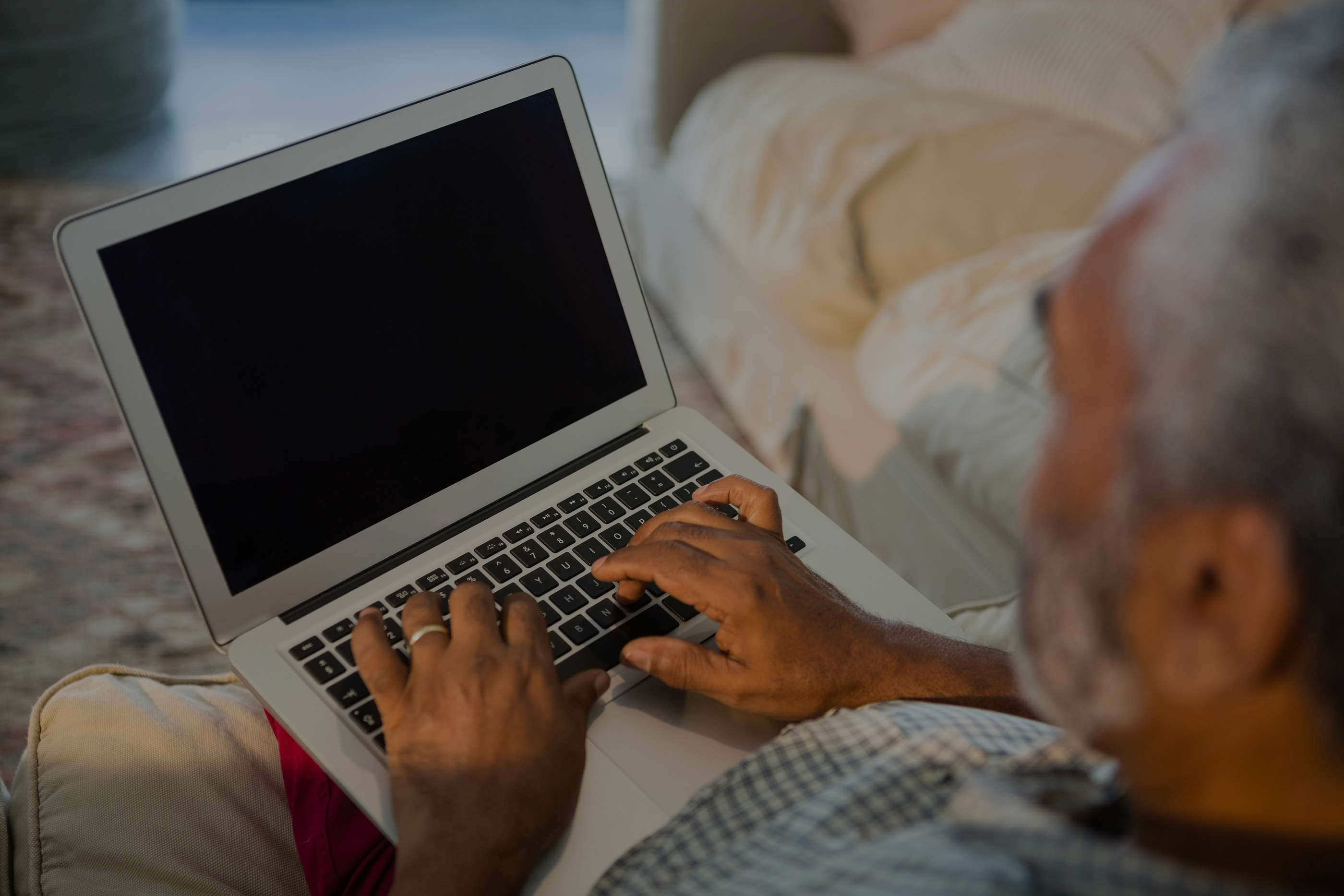 Senior man using laptop in the living room at home