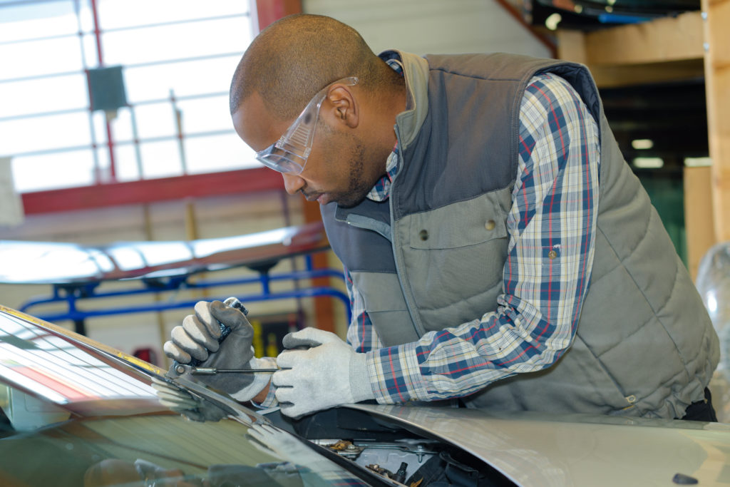mechanic using repairing equipment to fix damaged windshield