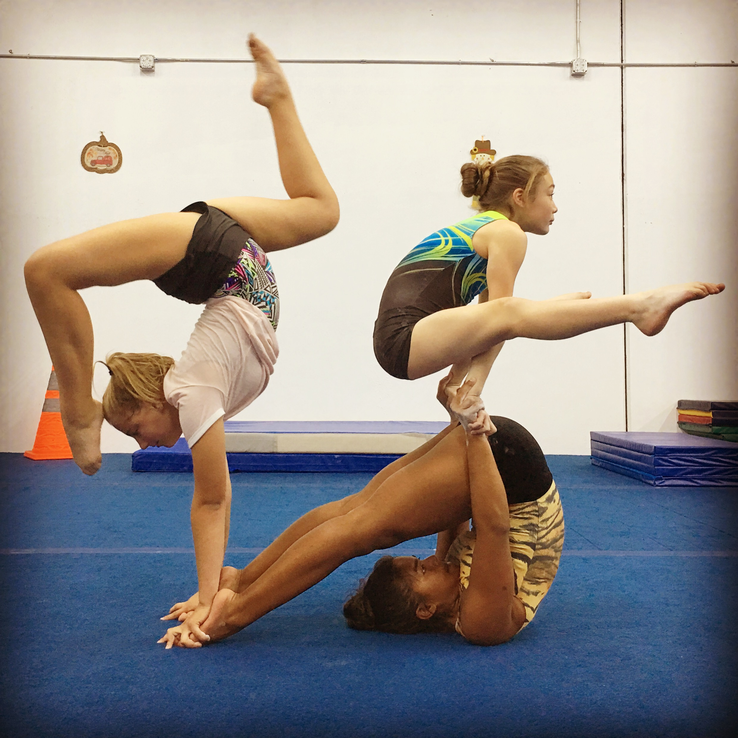 3 young ladies practicing acrobatic gymnastics at AGA