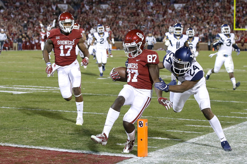 Oklahoma's Myles Tease (87) scores a touchdwon in front of West Virginia's Hakeem Bailey (24) during a college football game between the Oklahoma Sooners (OU) and the West Virginia Mountaineers at Gaylord Family-Oklahoma Memorial Stadium in Norman, Okla., Saturday, Nov. 25, 2017. Oklahoma won 59-31. Photo by Bryan Terry, The Oklahoman