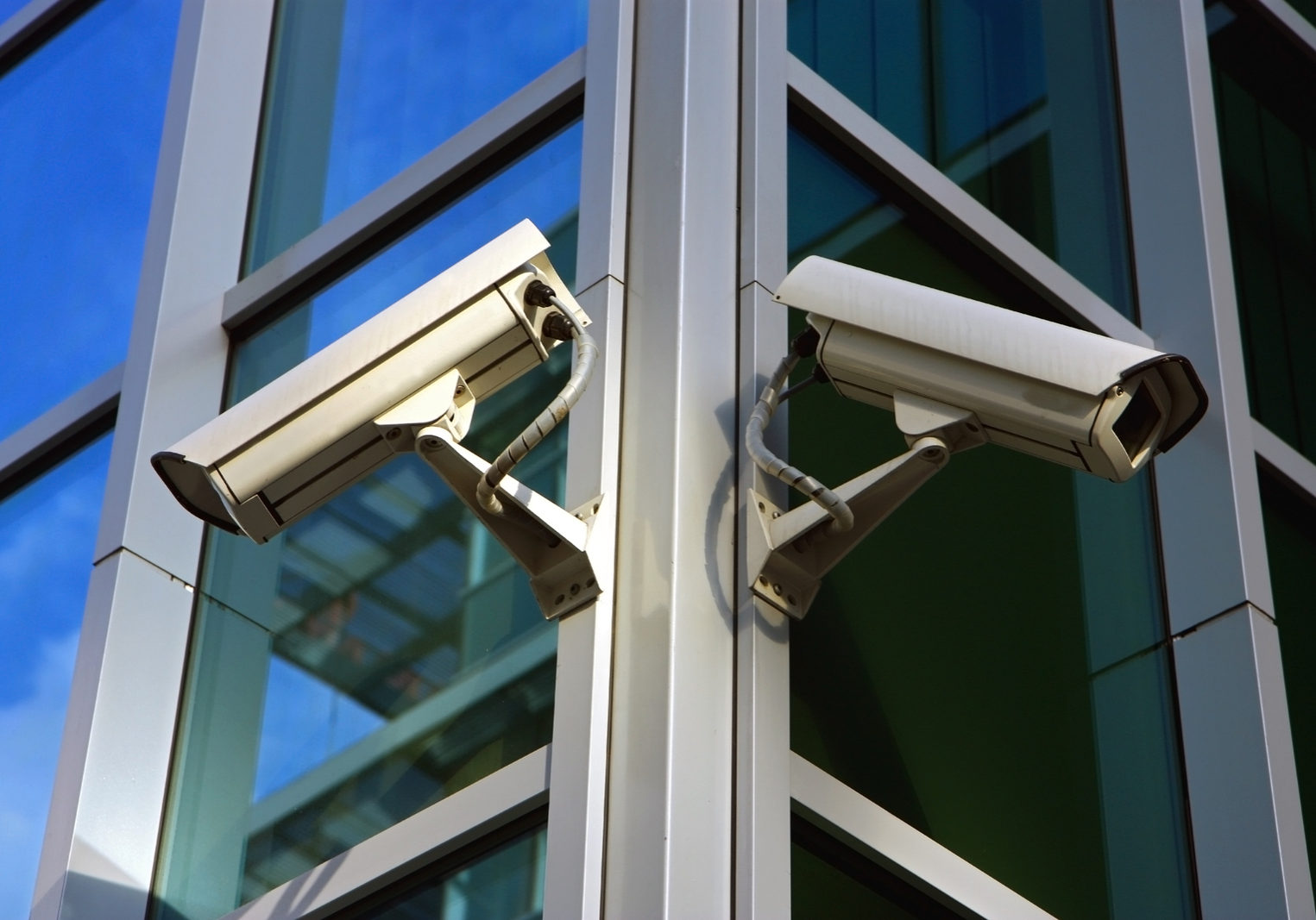 two city security cameras on the glass facade