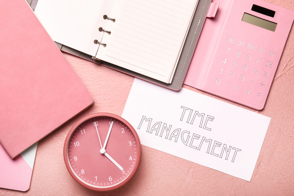 Alarm clock with stationery and text TIME MANAGEMENT on color background