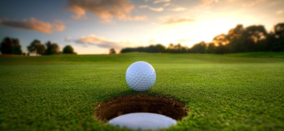 Golf ball rolling into cup