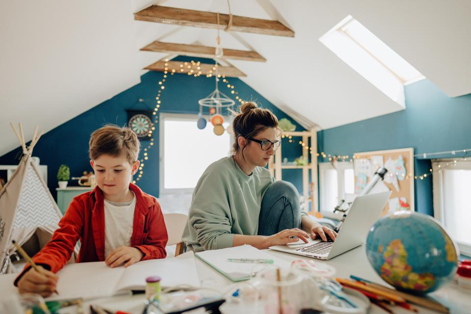 A woman works on her computer while a young boy does his homework in the same room.