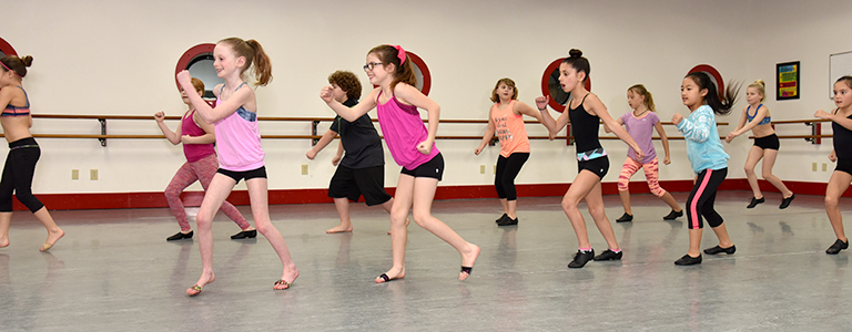 Elementary aged dancers participate in jazz lessons