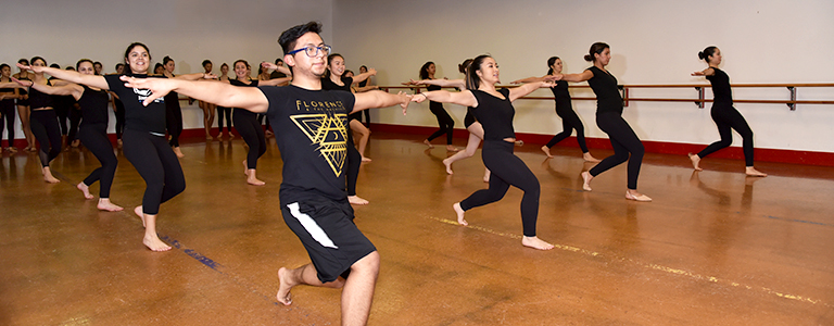 Competitive team dancers warm up in jazz technique class