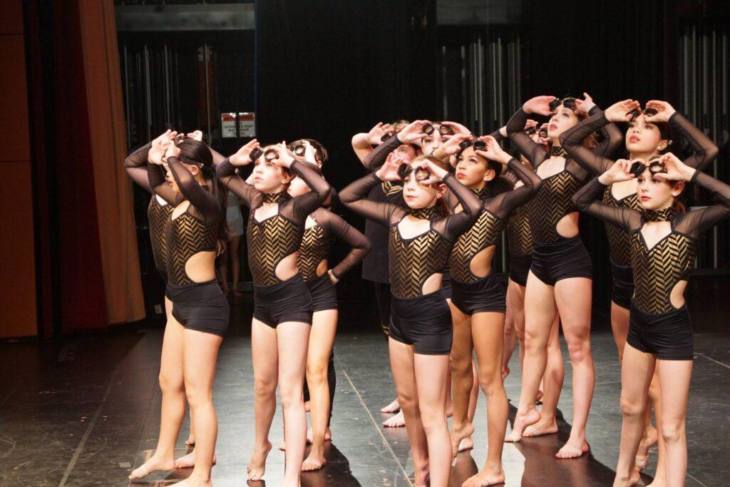 Dancers on stage wearing black