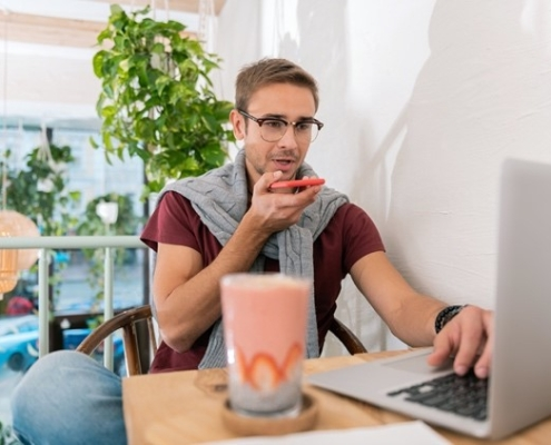 Nutritionist sitting at laptop with smoothie