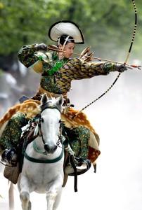 An archer in ancient samurai warrior uniform ridin