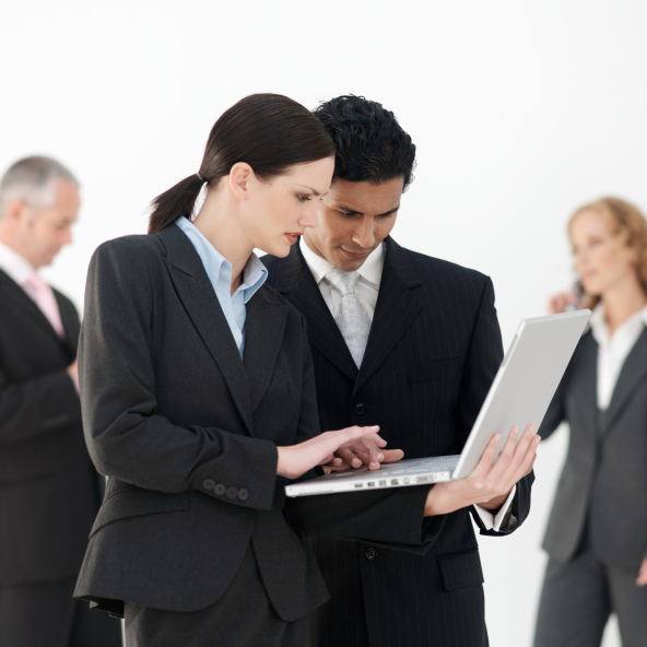 Business man and woman using laptop, others in background