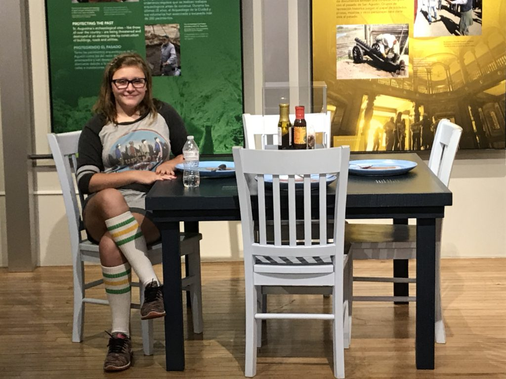Teen girl sitting at dinner table in St Augustine Cultural Center