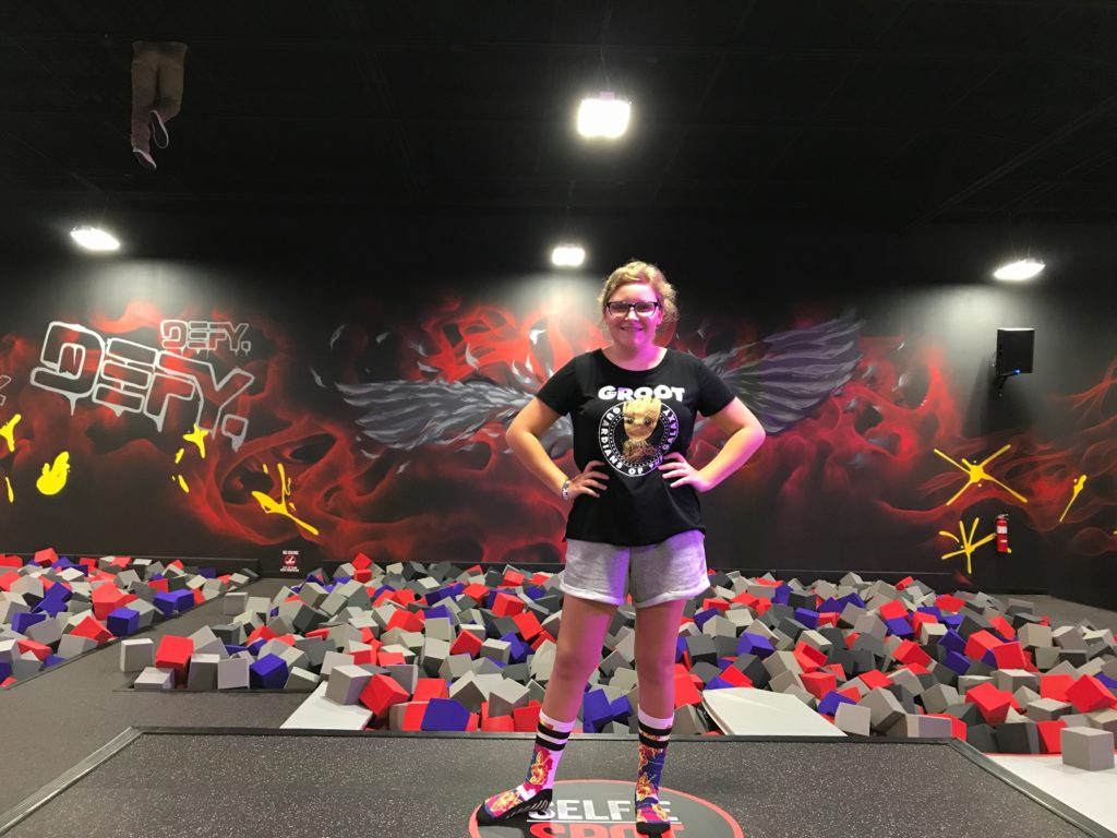 teen girl in front of wings wall