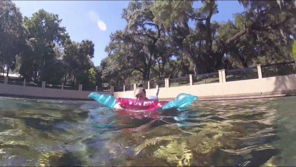 girl in springs swimming area on pool floats