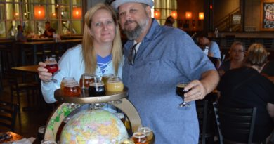 Couple standing with globe of beer at Perrin Brewing
