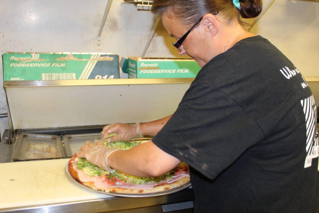Dan & Vi's employee making a deli slice pie