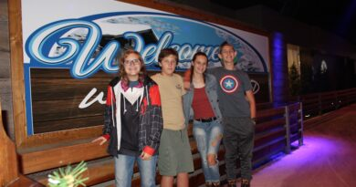 Teens standing in front of Winterland Adventures sign