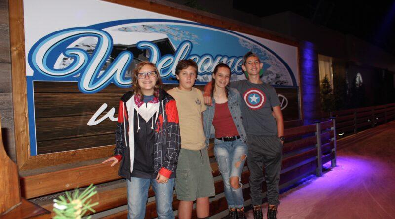 Teens standing in front of Winterland Adventures sign