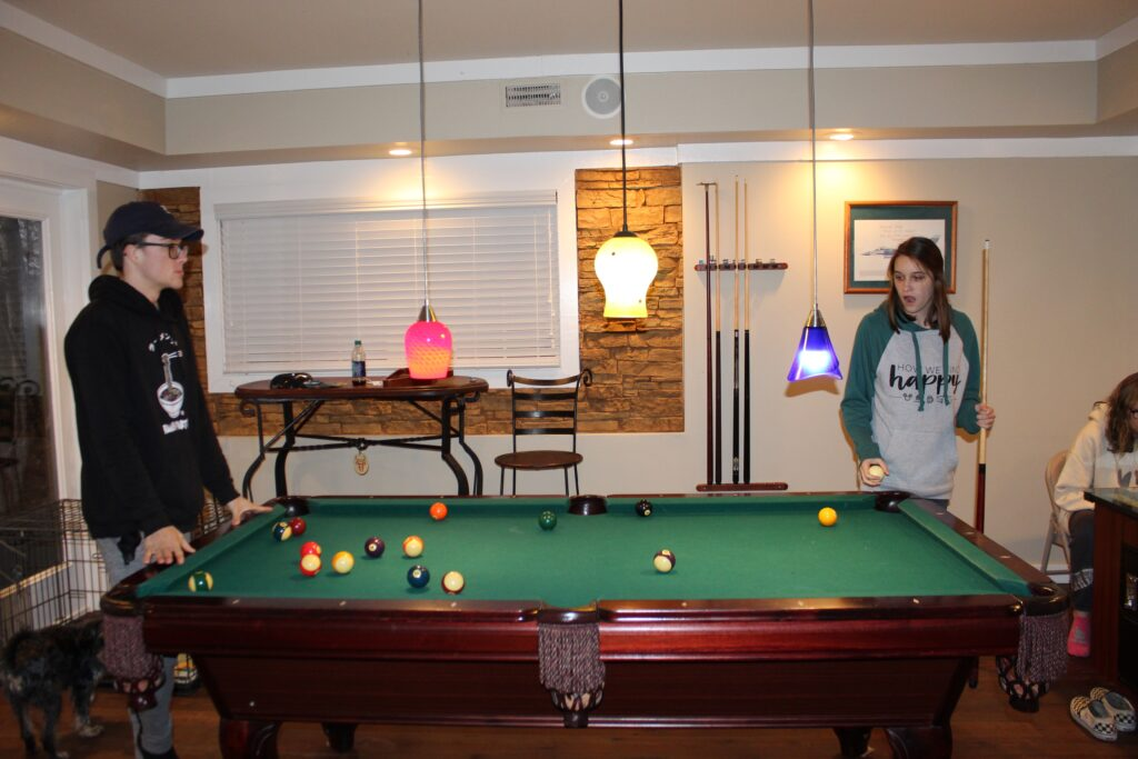 Teens playing pool at Southern Water's Retreat
