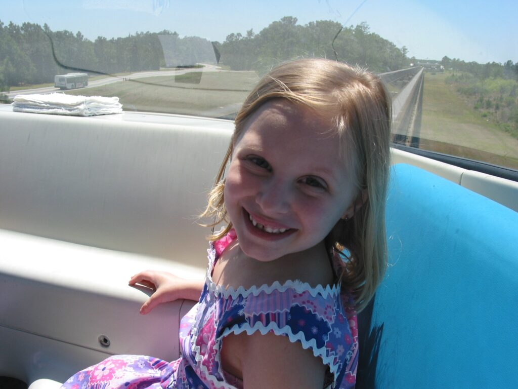 Young girl in monorail driver car