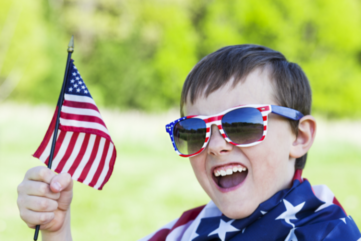 young boy holds american flag on the fourth