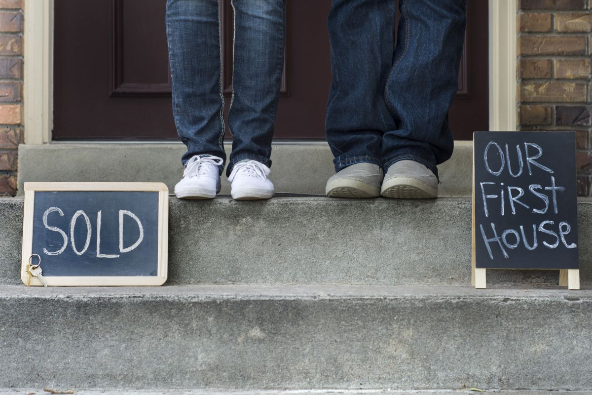First time home buyers on front steps of their new home
