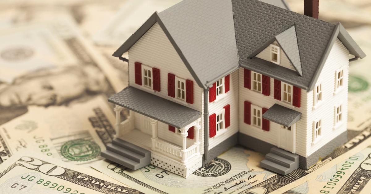 small model home sitting on dollar bills