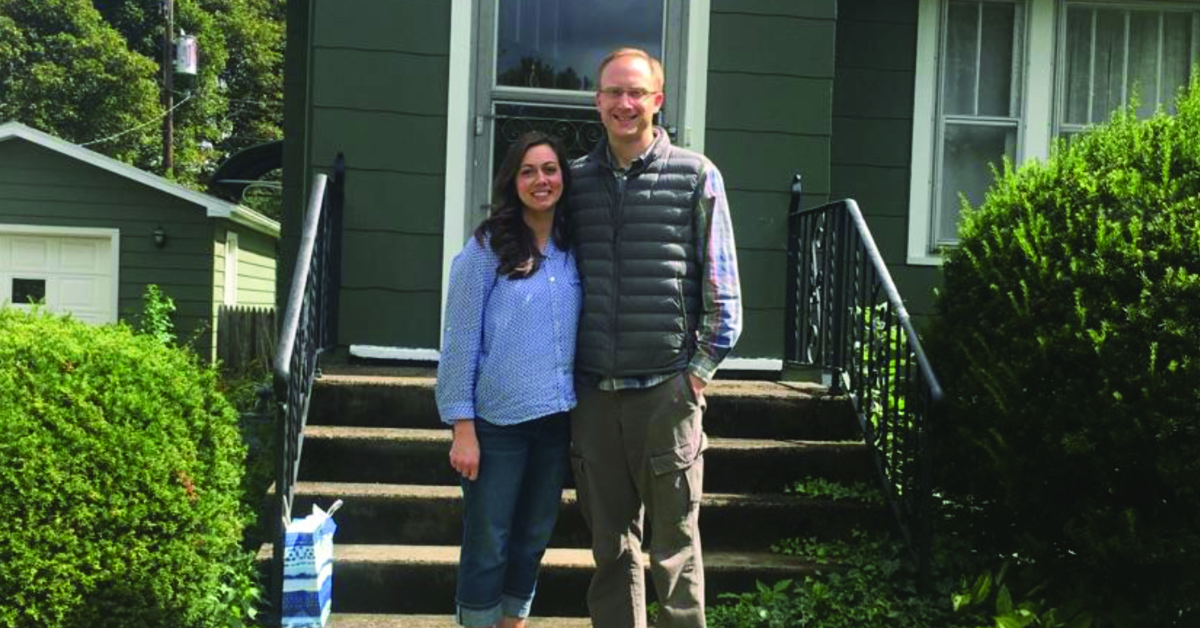 Couple with the keys to their new home in front of the house