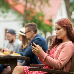 woman on phone at dinner. all in