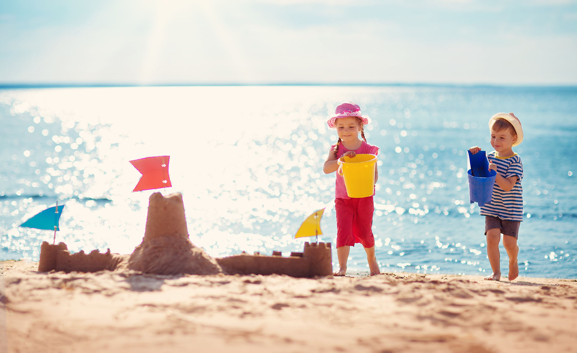 Two kids playing on the beach and building a sand castle