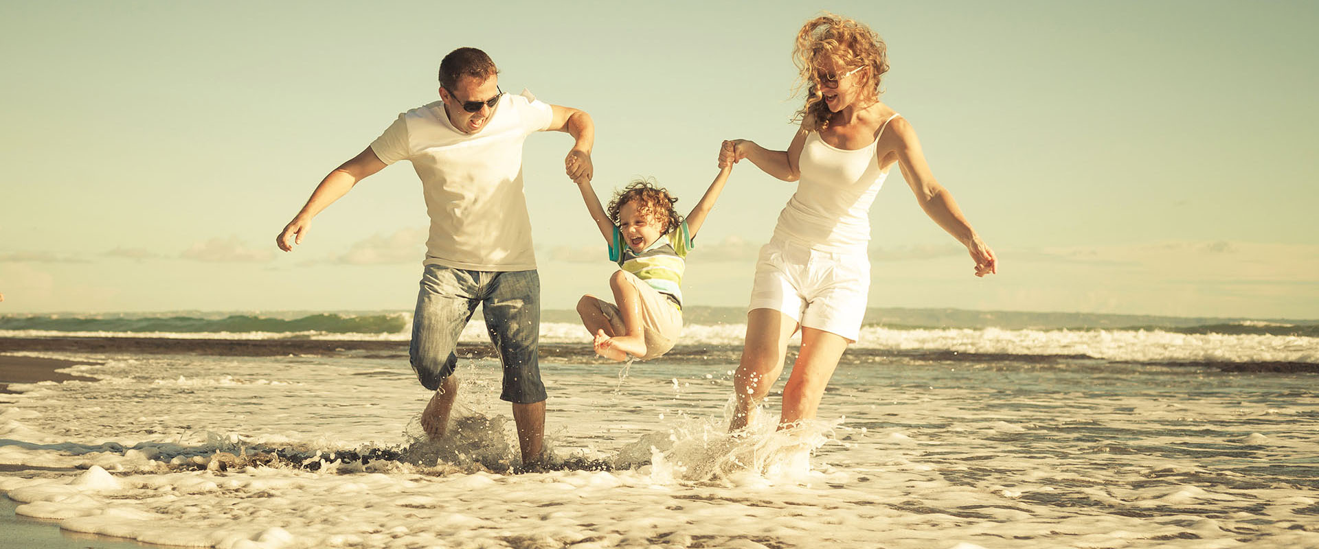 Couple holding hands with their child as they jump in the water at the beach