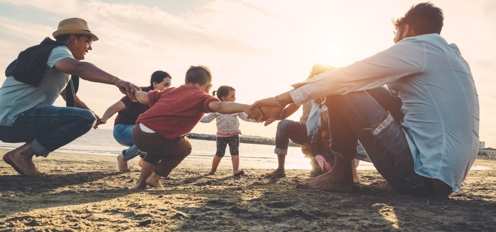 Family gathered and holding hands on the beach