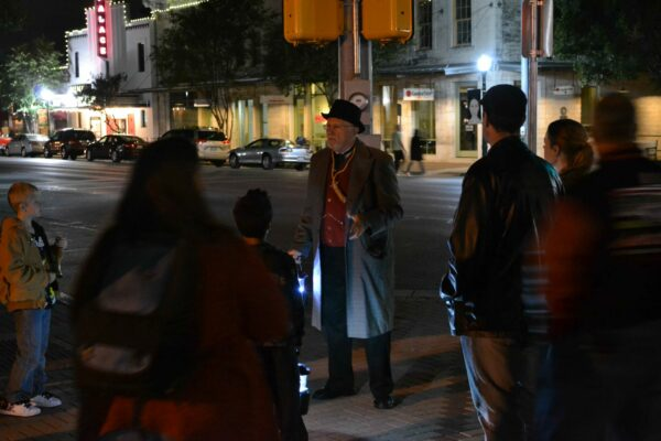 Costumed man leading ghost tour