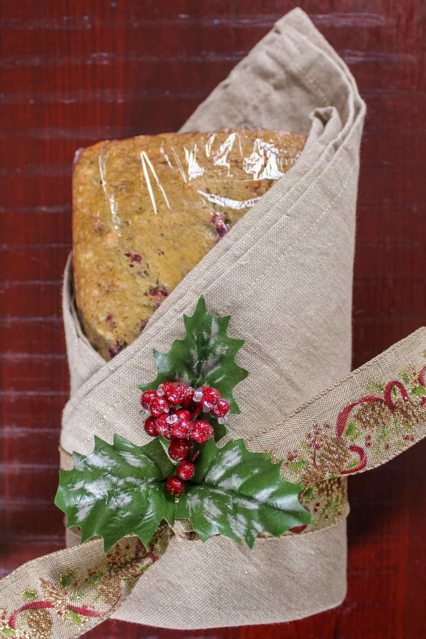 cranberry nut bread wrapped in cloth and tied with a ribbon