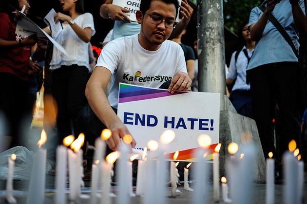 MANILA, PHILIPPINES - JUNE 14: A youth activist light candles as they gather for a vigil in solidarity with the victims of the mass shooting at the Pulse nightclub in Orlando, Florida on June 14, 2016 in Manila, Philippines. 49 people were killed after a gunman opened fire at nightclub frequented by gays lesbians and transgender people in the deadliest mass shooting in US history. (Photo by Dondi Tawatao/Getty Images)