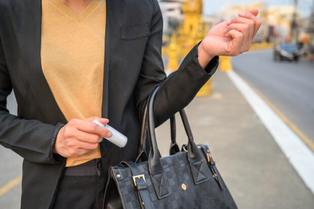 woman keeping hand sanitizer in her bag