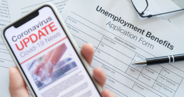 covid19 scams displayed on phone over unemployment papers