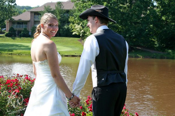 Bride and groom near pond.