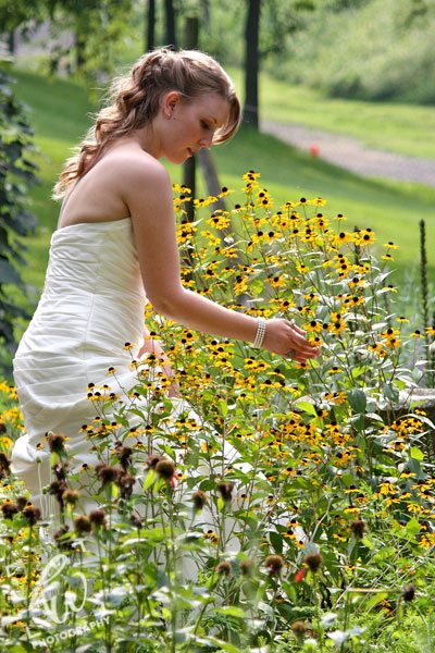 Bride picking flowers during wedding photography session in Pennsylvania.