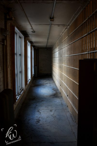 Eerily lit walkway of the vacant section of a New Jersey jail.