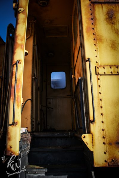 A look inside a yellow, rusting train car.